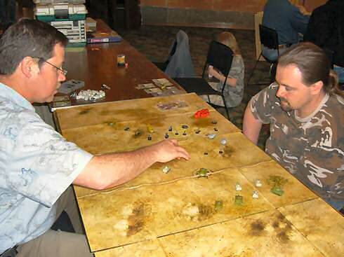Tom Crownhart, left, of Ada, Ohio, faces off against his friend Scott Howard, right, also of Ada, Ohio. The two were playing a game of Axis and Allies miniatures on the new desert theme maps with 3-inch scale-hexes.
